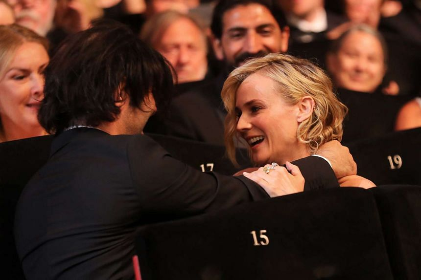 German actress Diane Kruger (centre) reacts next to German director Fatih Akin (left) after she was awarded with the Best Actress Prize for her part in 'Aus dem Nichts' (In the Fade) on May 28, 2017.
