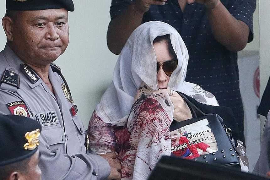 Australian Schapelle Corby being escorted by Bali police at the parole office in Denpasar, Indonesia, last Saturday.