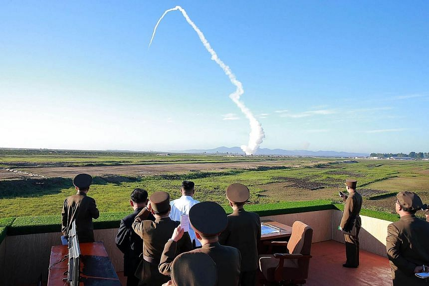 North Korean leader Kim Jong Un (in white shirt) watching a new anti-aircraft weapon system being launched during a test organised by the Academy of National Defence Science at an undisclosed location, in an undated photo released by KCNA yesterday.