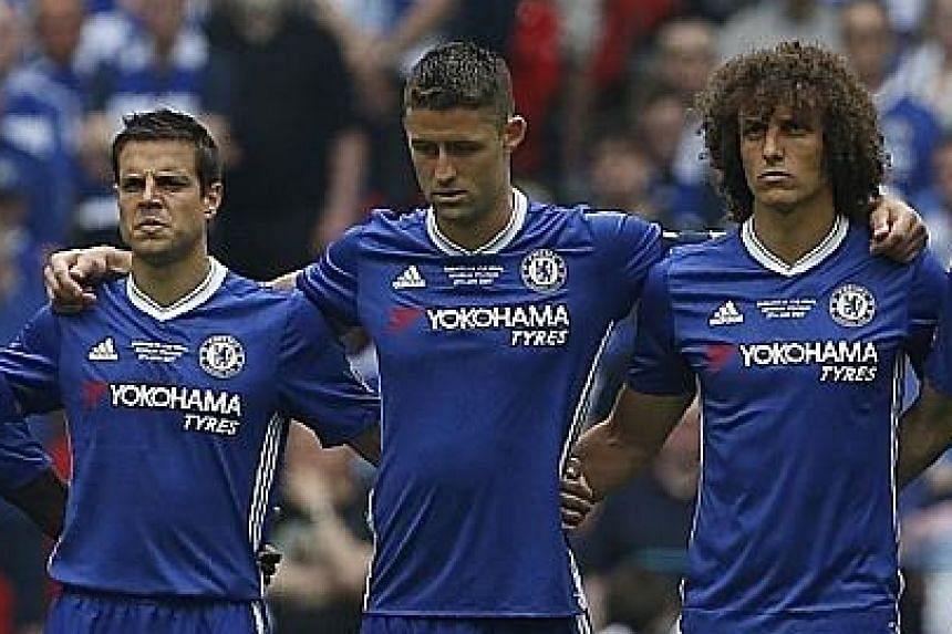 Chelsea's players, led by Gary Cahill (centre), observe a minute's silence in memory of the Manchester bombing victims. The Blues, however, initially forgot to wear black armbands.