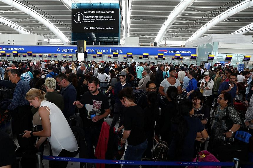 Passengers waiting at Heathrow Airport's Terminal 5 yesterday. Thousands were stranded after hundreds of BA flights at Heathrow and Gatwick were affected by the IT outage.