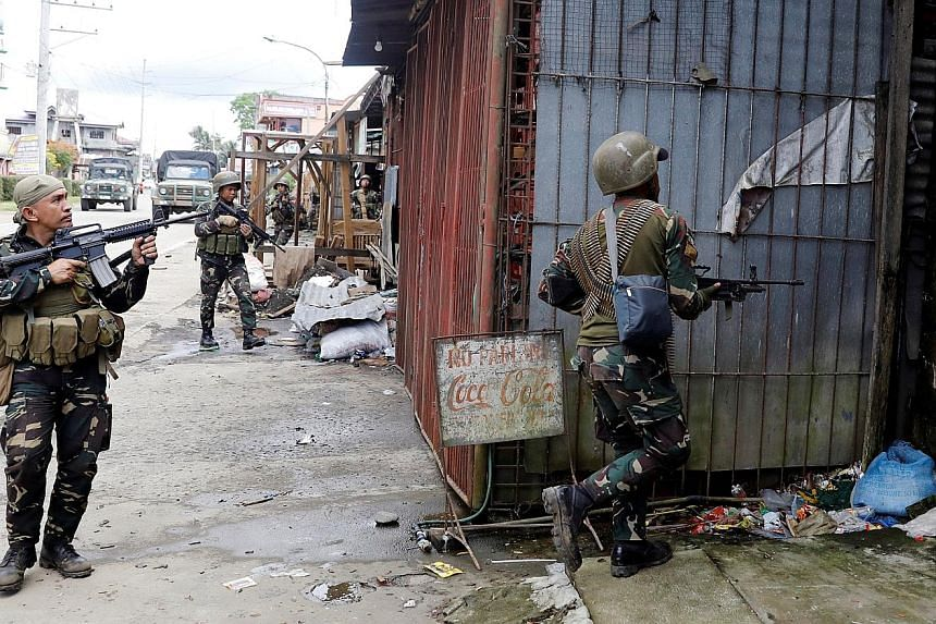 Left: Empty shells and bullets retrieved near the site where the bodies were found outside Marawi City. The grisly discovery confirms speculation that Maute rebels had killed civilians during a takeover of Marawi - a move the military believes is aim
