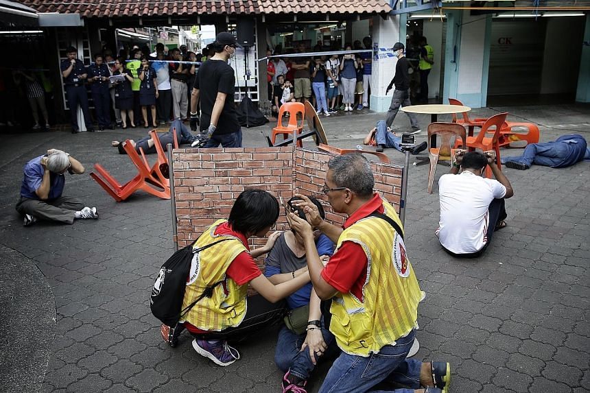 """Members of a Community Emergency Response Team helping a """"victim"""" and providing information to the police during a mock terror attack on a coffee shop in Yishun yesterday. Residents also learnt how to help someone having a heart attack and register f"""