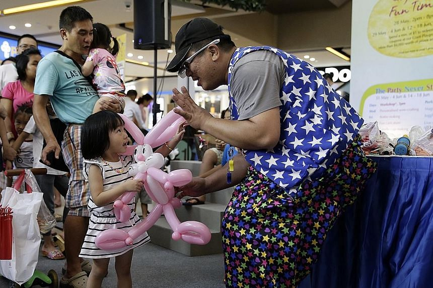 Three-year-old Gwendolyn Sim getting a balloon sculpture made by Mr Chia Meng Choon, 42, better known as Mr Lightning Fingers, yesterday at an event to celebrate The Seletar Mall's second anniversary. During the two-hour balloon sculpting segment of