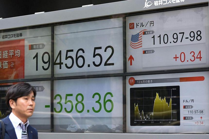 A pedestrian walking past a quotation board flashing the key Nikkei index of the Tokyo Stock Exchange in Tokyo, on May 18, 2017.