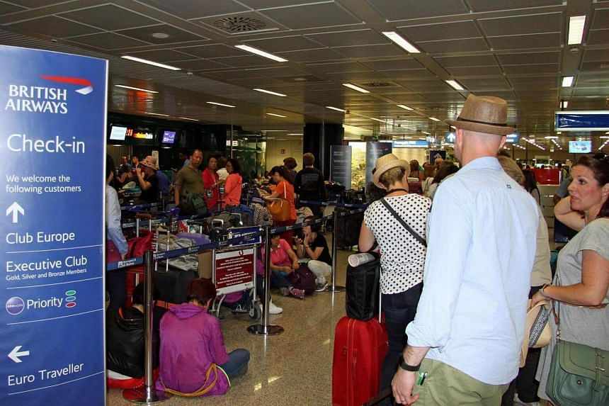 Passengers stand at the British Airways check-in desk in Fiumicino, near Rome, on May 27, 2017.