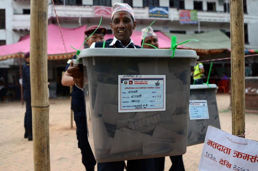 A Nepalese election worker carrying a sealed ballot box after polling stations closed in Kathmandu on May 14. The second round of voting has been postponed.
