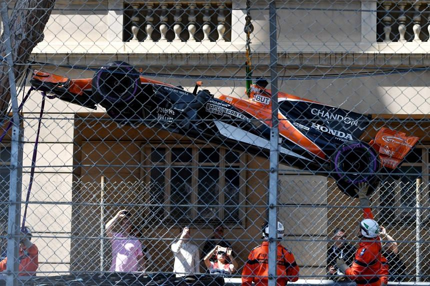 Race marshals lift the car of McLaren's British driver Jenson Button after he crashed with the car of Sauber's German driver Pascal Wehrlein (not pictured) during the Monaco Formula 1 Grand Prix at the Monaco street circuit, on May 28, 2017 in Monaco