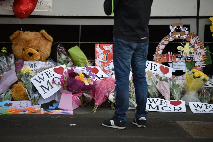 Well wishers look at messages of support and floral tributes to the victims of the Manchester attack,outside the Manchester Arena Complex in Manchester on May 27, 2017.