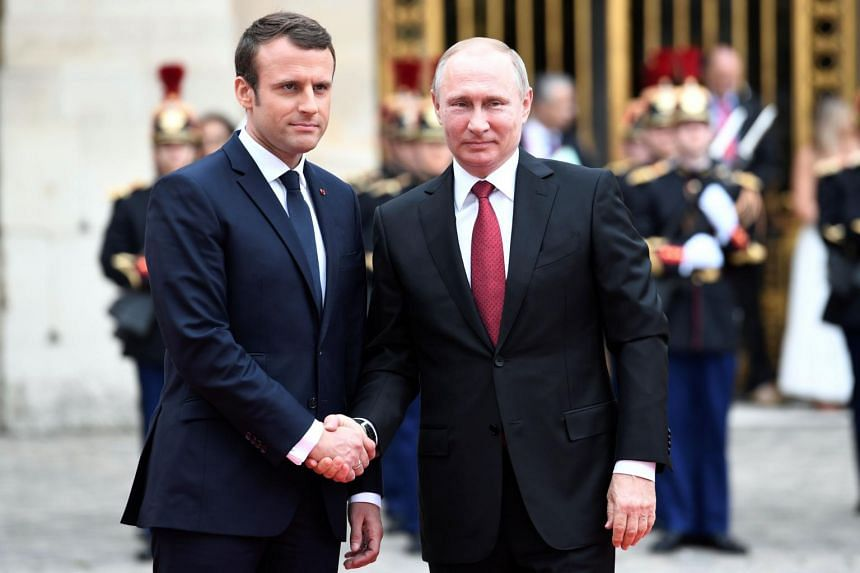 Russian President Vladimir Putin (right) is welcomed by French President Emmanuel Macron as they shake hands at the Versailles Palace, near Paris, on May 29, 2017, ahead of their meeting.