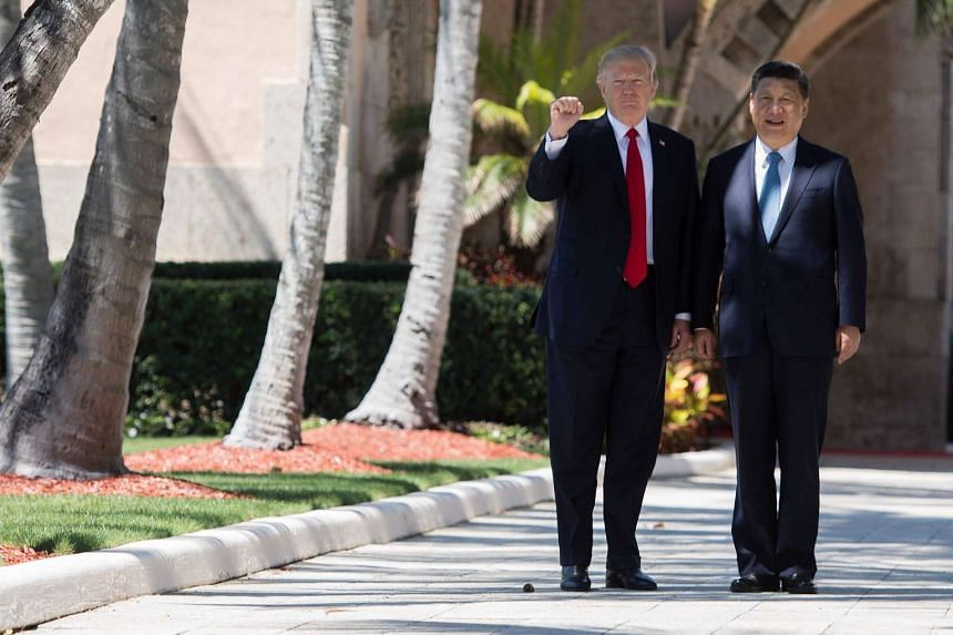 US President Donald Trump (left) pumps his fist as he and Chinese President Xi Jinping (right) walk together at the Mar-a-Lago estate in West Palm Beach, Florida on April 7, 2017.