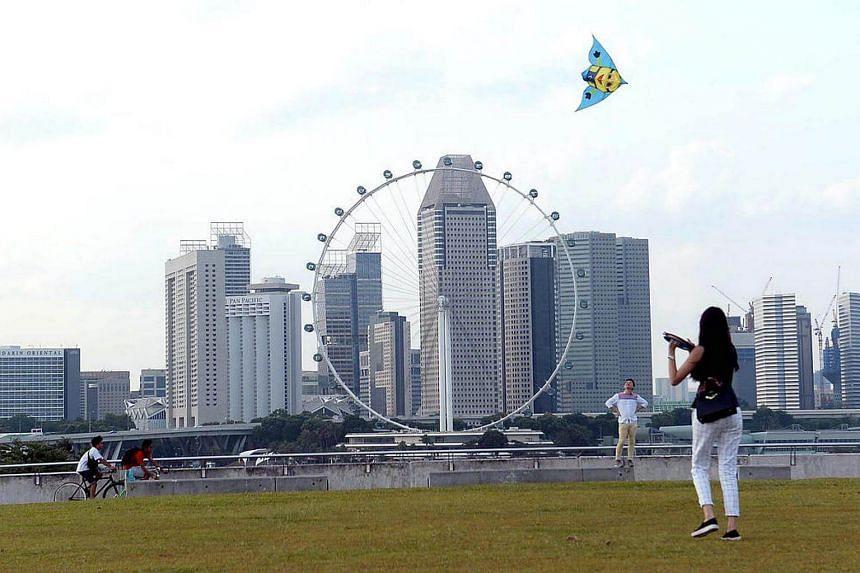 A woman flying a kite at the Marina Barrage.