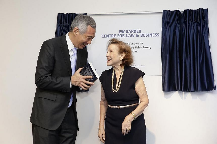 Prime Minister Lee Hsien Loong receiving the book EW Barker: The People's Minister from E W Barker's wife, Mrs Gloria Barker, after the official launch of the EW Barker Centre for Law and Business on May 29, 2017.