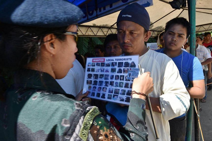 """A police officer checks the identity of a resident against a chart with images of """"local terrorists"""" at a checkpoint at the entrance to Iligan City, on May 29, 2017."""