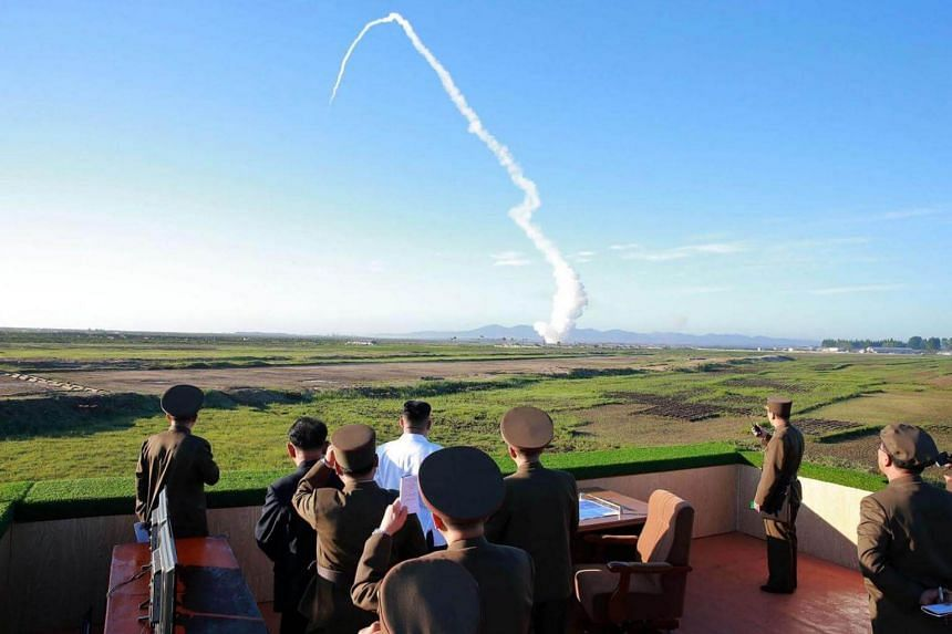 North Korean leader Kim Jong Un watching the test of a new anti-aircraft guided weapon system organized by the Academy of National Defence Science at an undisclosed location.