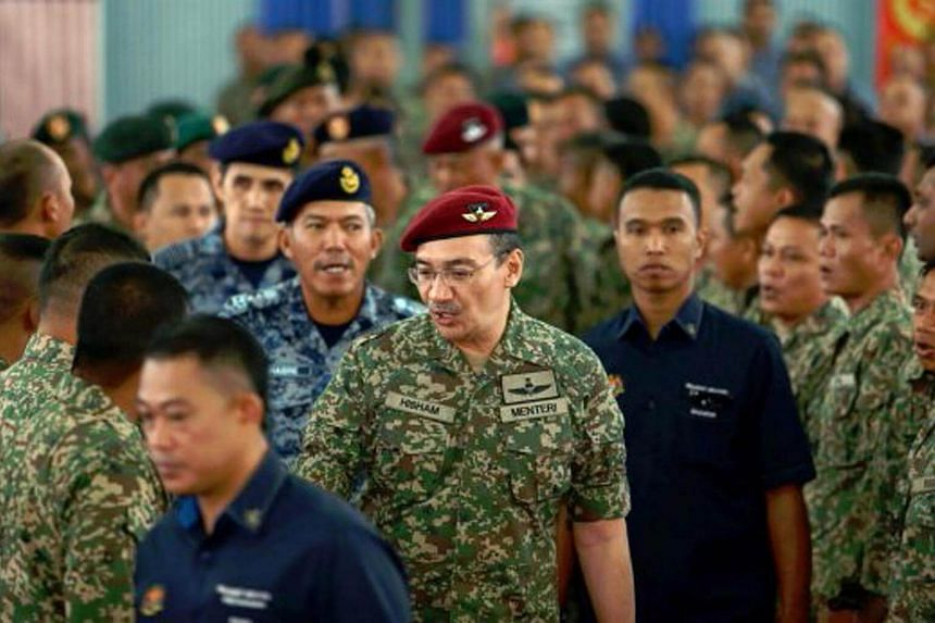 Malaysia's Defence Minister Hishammuddin Hussein (centre) with Armed Forces personnel.