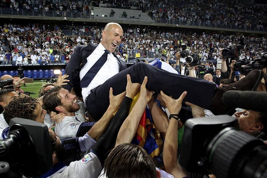 Real Madrid players toss their coach Zinedine Zidane as they celebrate winning the League championship on May 21, 2017.