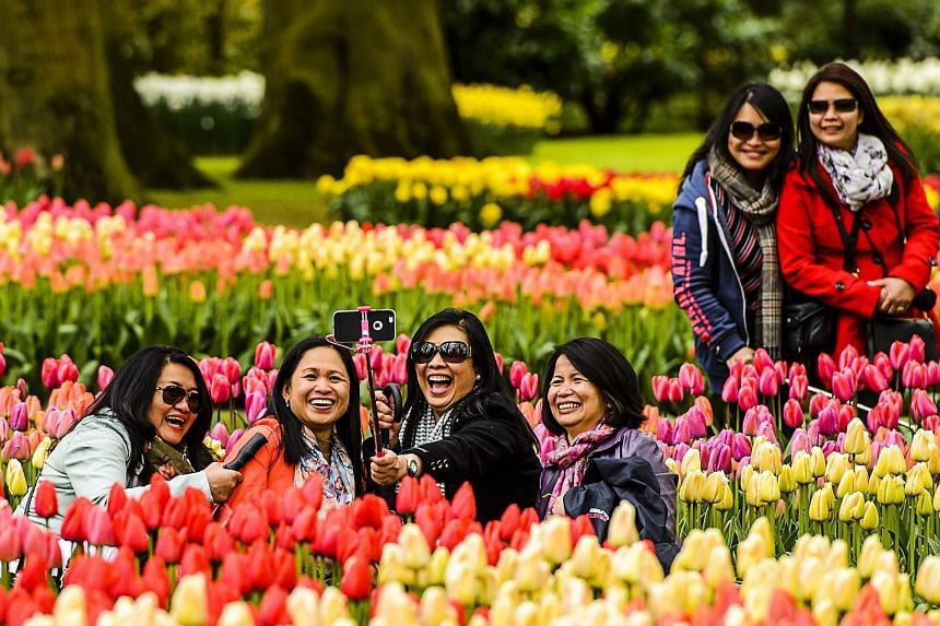 Tourists taking a photograph among flowers at the Keukenhof garden in Lisse, Netherlands, on April 28, 2016.