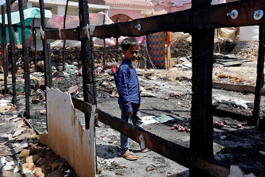 A boy belonging to Rohingya Muslim community stands amidst the rubble of a burnt shop, on May 5, 2017.