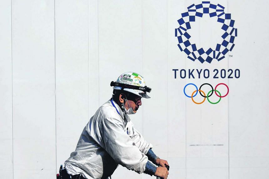 A construction worker walks past at a construction site of a building displaying Tokyo 2020 Olympics emblem in Tokyo.