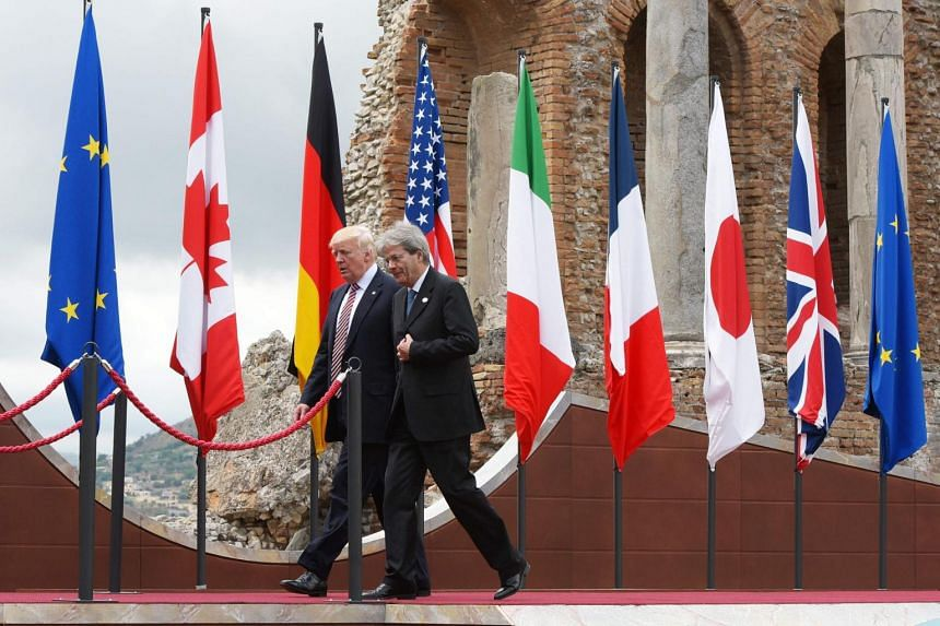 Italy's Prime Minister Paolo Gentiloni walks with US President Donald Trump ahead of the family photo at the Greek Theatre during the G7 Summit in Taormina, on May 26, 2017.