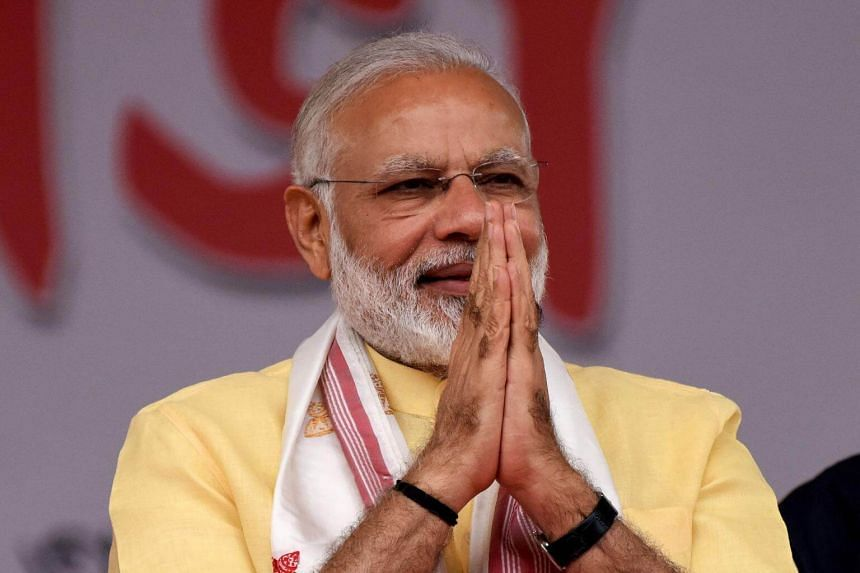 Indian Prime Minister Narendra Modi greets his supporters during the celebration marking the National Democratic Alliance government's three years in power at the Khanapara Veterinary ground in Guwahati, India, on May 26, 2017.
