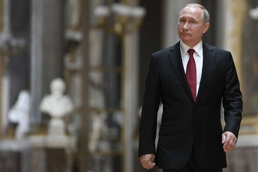 Russian President Vladimir Putin walks in the Galerie des Batailles (Gallery of Battles) as he arrives for a joint press conference with French President Emmanuel Macron.