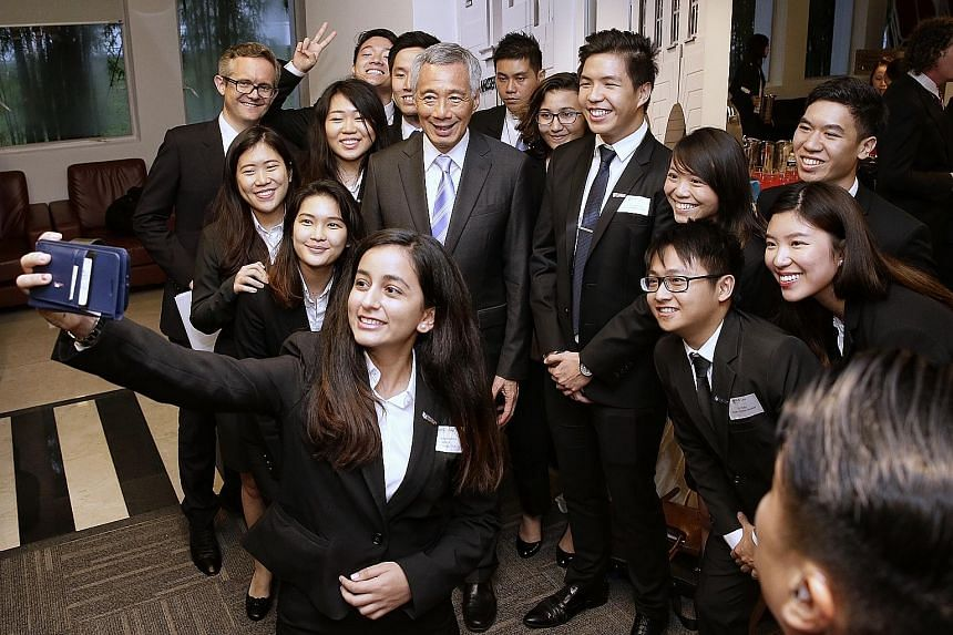 Above: Prime Minister Lee Hsien Loong receiving the book E.W. Barker: The People's Minister from Mrs Gloria Barker after the launch of the EW Barker Centre for Law and Business. Left: PM Lee and NUS law dean Simon Chesterman taking a wefie with stude