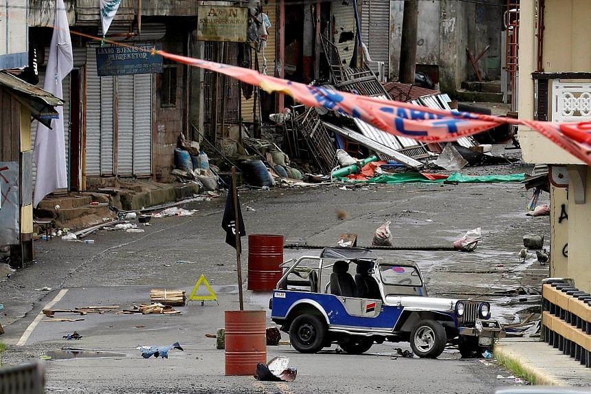 A Filipino soldier keeping a watchful eye as fighting continues between the Islamist militants and government forces in Marawi on Sunday. Above: A black ISIS flag is seen in a militant stronghold in the city yesterday. The Philippine military's spoke