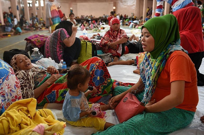 A family from Marawi resting at an evacuation centre in Balo-i, Mindanao, yesterday. Many more locals are stuck in their homes and are afraid to venture out for fear that militants roaming the streets would kill them or take them hostage.