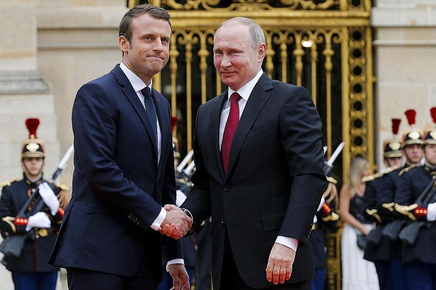 French President Emmanuel Macron (left) with Russian President Vladimir Putin at Versailles, near Paris yesterday. Mr Macron will use an exhibition on Peter the Great at the palace to try to get bilateral ties off to a new start.