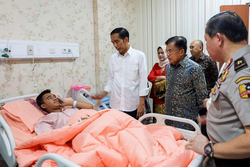Indonesian President Joko Widodo and Vice-President Jusuf Kalla visit a bomb blast victim at the police hospital in Jakarta, Indonesia, on May 25, 2017.