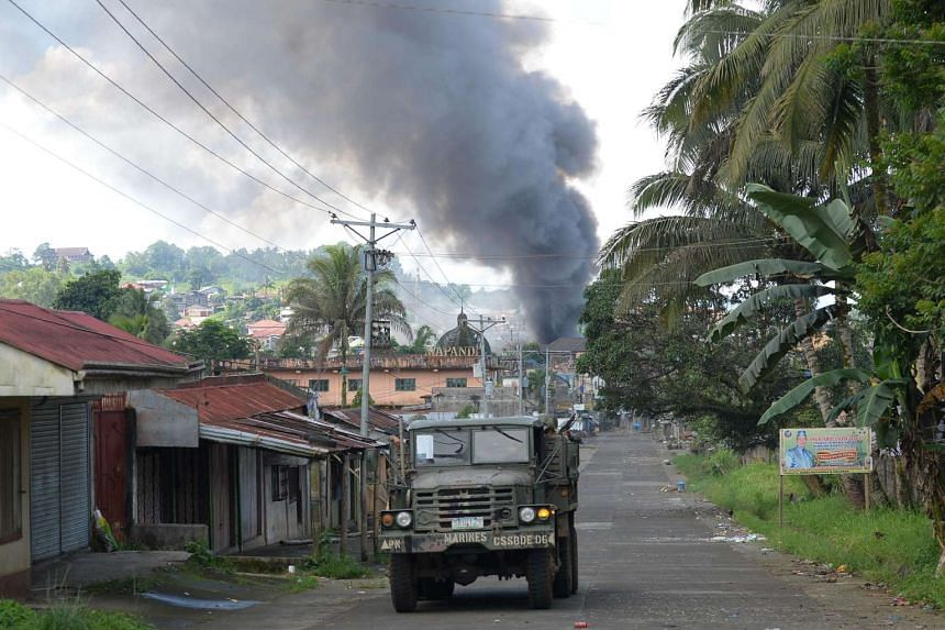A Philippine Marines truck speeds away as black smoke billows from burning houses in Marawi on the southern island of Mindanao on May 30, 2017.