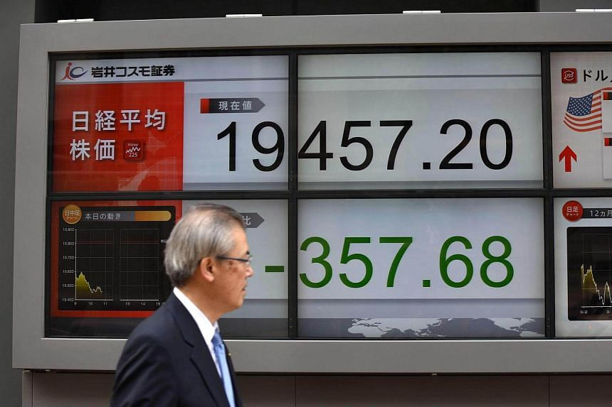 A pedestrian walks past a stock quotation board flashing the key Nikkei index of the Tokyo Stock Exchange.
