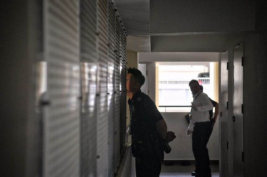 A policeman peers through the corridor on one of the lower floors at block 520A.