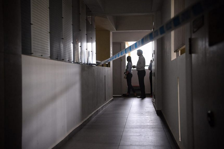 Policemen stand outside the unit at block 520A.