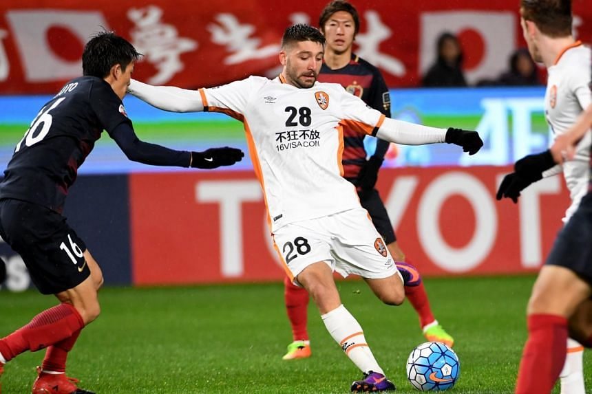 Brisbane Roar forward Brandon Borrello (centre, left) shoots the ball in front of Kashima Antlers defender Shuto Yamamoto (left) during a AFC Champions League football match, on March 14, 2017.