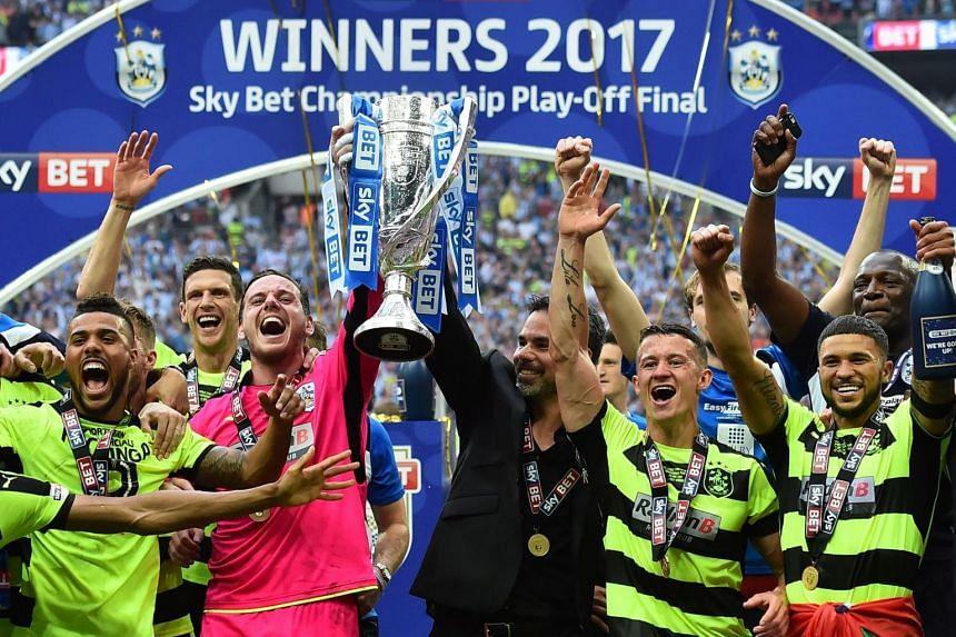 Huddersfield Town's Welsh goalkeeper Danny Ward (centre, left) and Huddersfield Town's German head coach David Wagner (centre, right) hold up the Championship Playoff trophy.