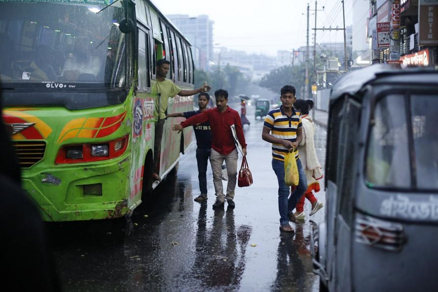 People try to get on a bus during rainy weather in the streets in Dhaka, Bangladesh, on May 29, 2017.
