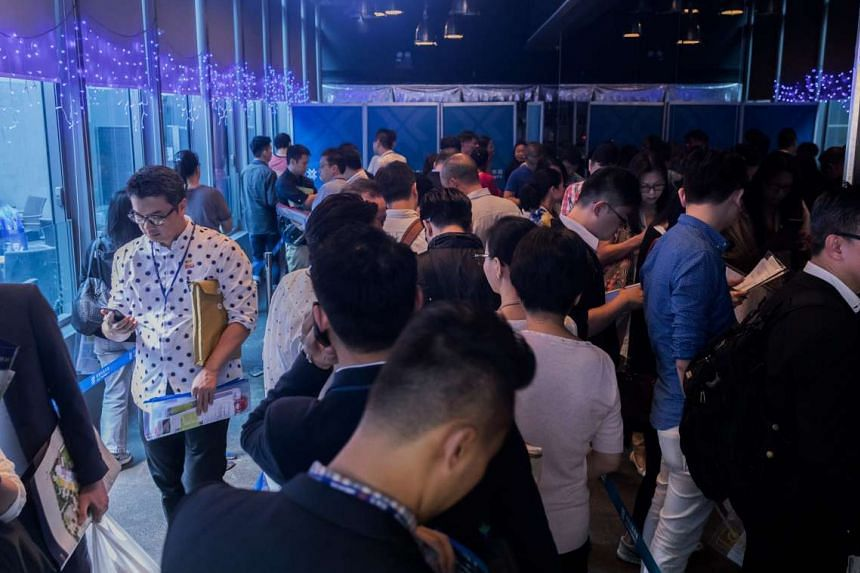 Real estate agents and potential buyers waiting in line outside the sales office of Victoria Skye residential development in Hong Kong.