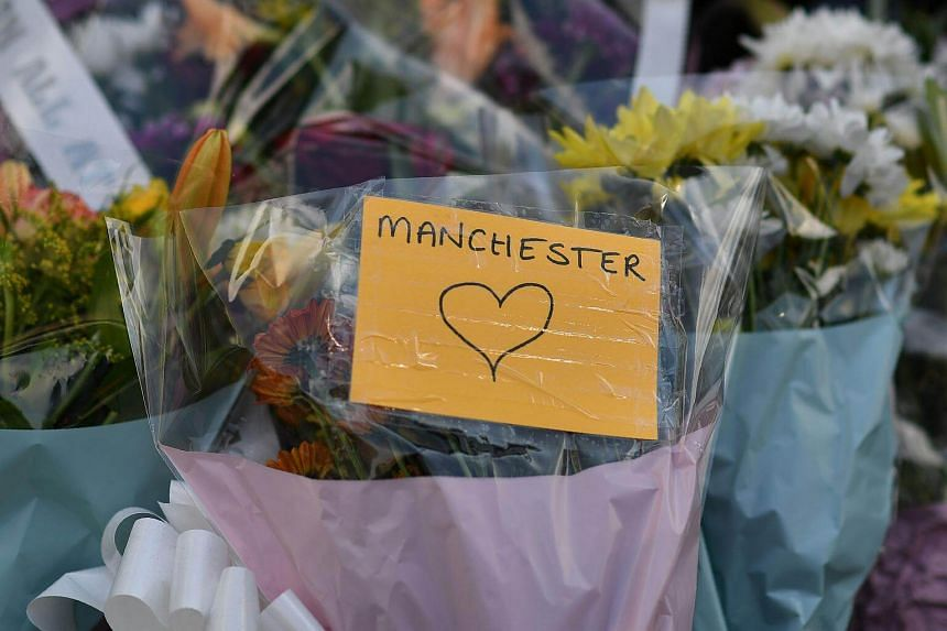 Flowers and messages of support are seen outside Victoria Station car park, near the Manchester Arena, in tribute to victims of the bombing, on May 25, 2017.