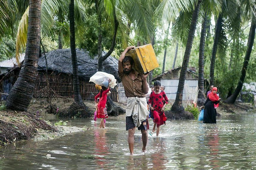 Bangladeshi residents walking with their belongings towards a safer area near the coastal line at the Cox's Bazar district in the Chittagong, on May 30, 2017.