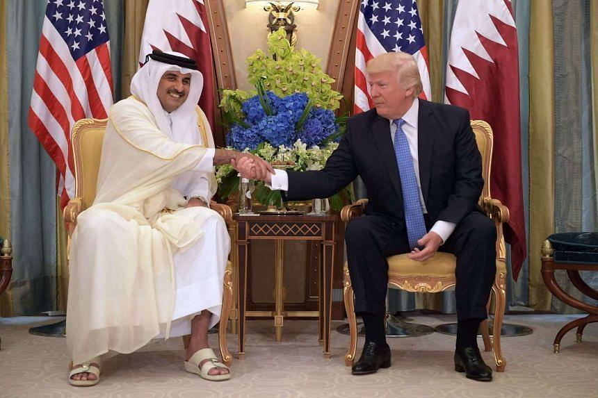 US President Donald Trump and Qatar's Emir Sheikh Tamim Bin Hamad Al-Thani take part in a bilateral meeting at a hotel in Riyadh on May 21, 2017.