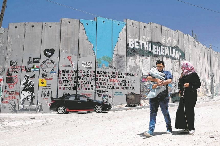 A Palestinian family walk past new graffiti painted on Israel's controversial separation barrier in the West Bank city of Bethlehem, on May 15, 2017.