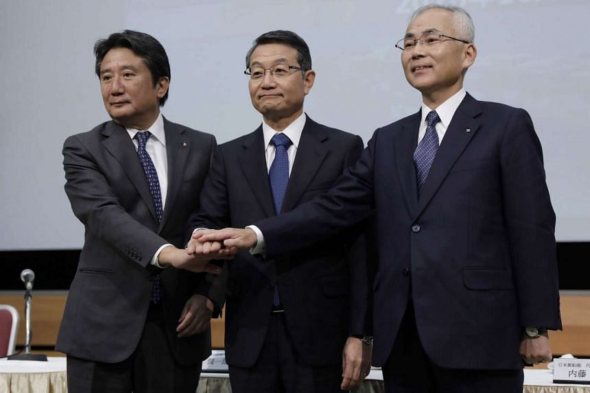 The presidents of Japan's big three shipping lines joining hands at a news conference in Tokyo on May 31.