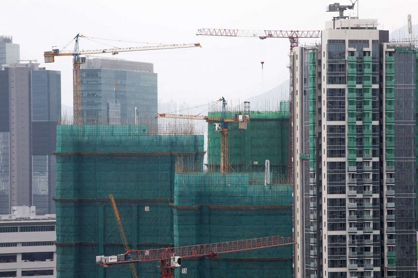 Cranes operating atop residential buildings under construction at the former Kai Tak airport area in Hong Kong on May 26.