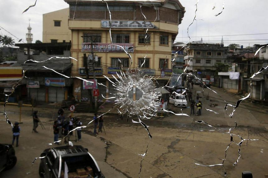A view of a street seen through a damaged window glass from a sniper bullet during fighting between government soldiers and rebels in Marawi City.