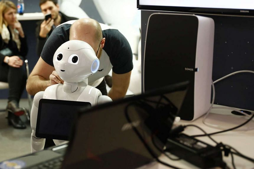 An employee works on a robot at the Soft Bank Robotics' stand during the Digital Business fair CEBIT in Hanover.