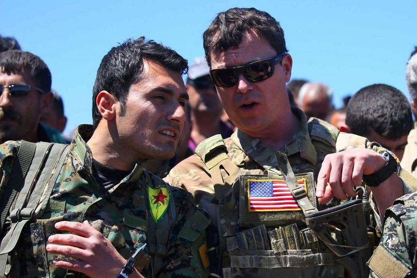 A US officer speaking with a fighter from the Kurdish People's Protection Units (YPG), April 25, 2017.