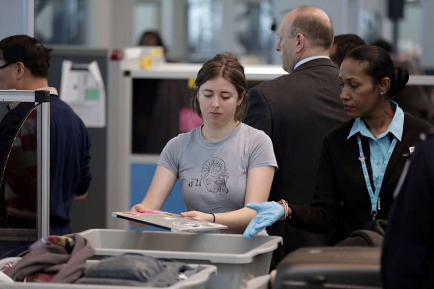 A traveller gives her laptop to an official before scanning her carry-on bags at JFK airport in New York City, May 17, 2017.